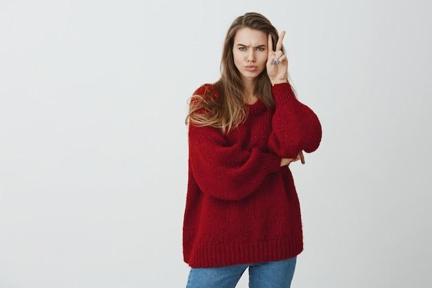 Не кукла, чтобы улыбаться все время. студийный снимок стильной симпатичной женщины в свободном свитере, показывающей знак победы или мира возле лица, нахмурившись и выражая неприязнь или обиду, стоя