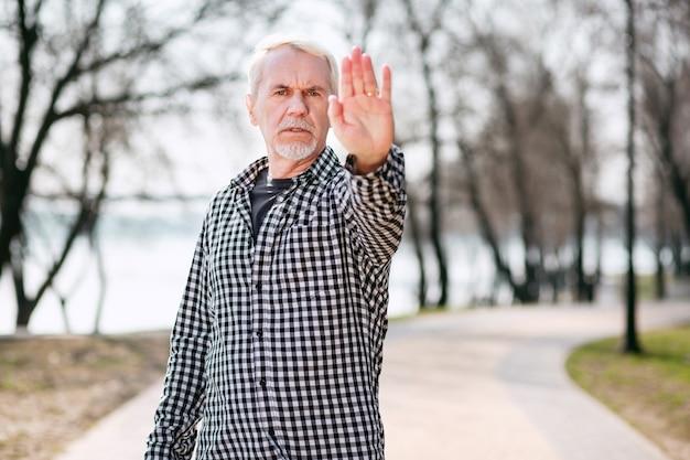 Не разрешено. серьезный старший мужчина, стоящий в парке и показывающий руку