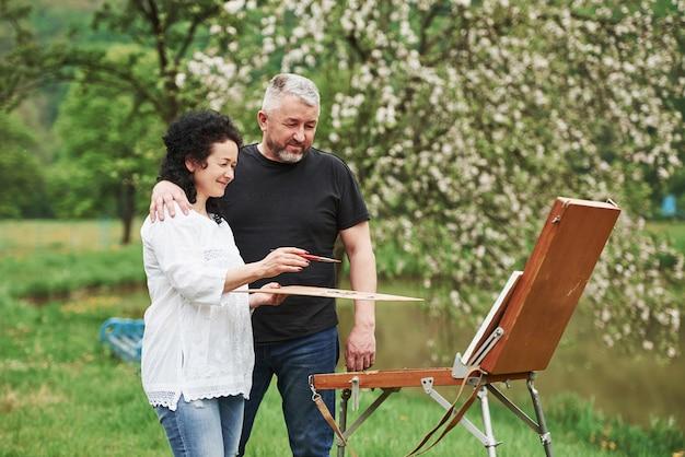 Совсем неплохо. пожилая пара отдыхает и вместе работает над краской в парке