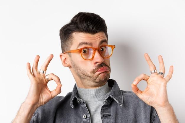 나쁘지 않다. 괜찮은 징후를 보여주는 세련된 안경에 감동 한 남자와 승인에 고개를 끄덕이며, 좋은 일을 칭찬하고, 칭찬을하고, 흰색 배경에 서 있습니다.