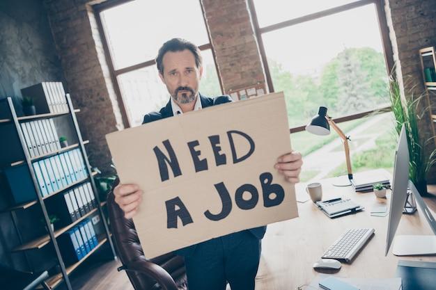 もう上司ではありません。不機嫌そうな絶望の写真悲しい解雇解雇された労働者成熟した男はプラカードのポスターを保持します新しい仕事最後の仕事日職場は機嫌が悪い現代のオフィスを屋内で解雇しました