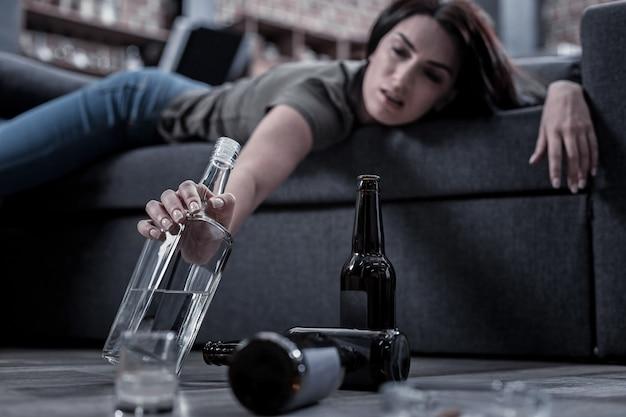 Недостаточно. селективный фокус бутылки с алкоголем, которую принимает пьяная несчастная женщина, лежа на диване