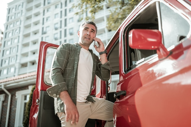 Недостаточно времени. сосредоточенный мужчина, ступивший на одной ноге в машину, отвечает на вопросы по телефону.