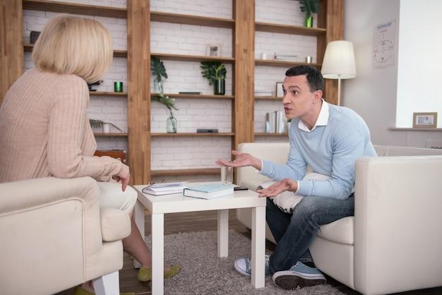 Не честно. обеспокоенный встревоженный мужчина разговаривает с психологом, позируя на диване