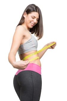 Эта лента больше не понадобится. вертикальный снимок великолепной молодой женщины в спортивной одежде, измеряющей ее талию, изолированную на белом
