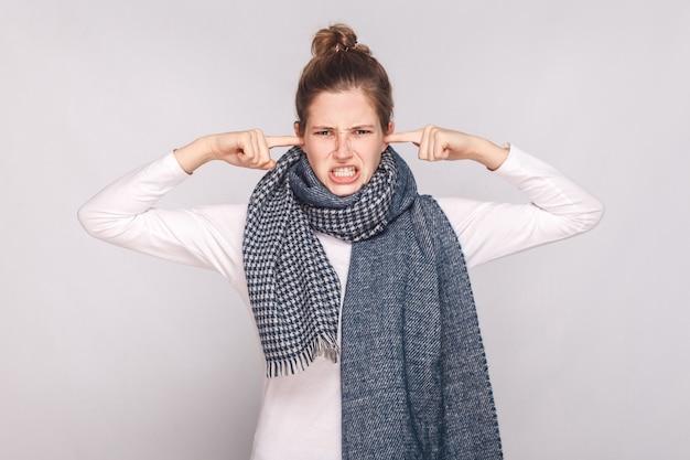 聞こえない!病気の若い女性が彼女の耳に指を触れています。スタジオショット