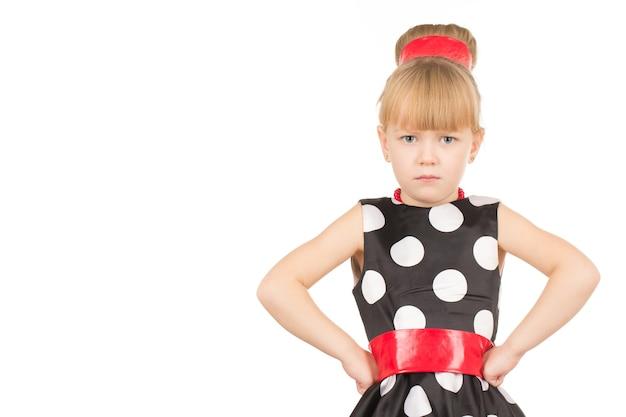 Не впечатлен тобой. студийный снимок маленькой девочки в платье, выглядящей сердитой