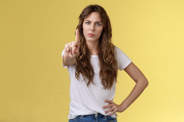 내 시계에 없습니다. 진지하게 보이는 자신감 넘치는 여성은 검지 손가락을 흔드는 금지 금기 제스처를 허용하지 않는 잔인한 금지된 불쾌한 얼굴을 내밀며 여성의 권리를 보호합니다.