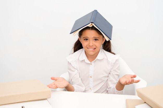 기억할 수 없습니다. 여자 아이 혼란 지친 책 지붕 머리 흰색 배경. 기억하려고 하는 것에 지친 여학생. 아이 교복 피곤한 얼굴. 여학생은 공부를 포기합니다.