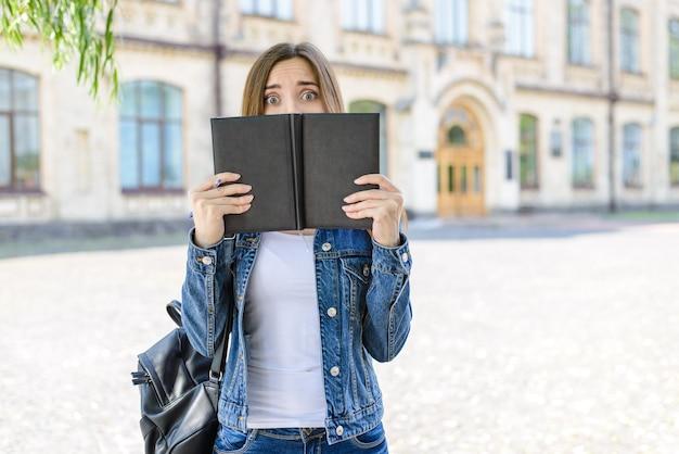 시험 준비가 안됐어! 입구 사람 사람들은 미친 불안 감정 표정 개념. 열린 책 뒤에 숨어있는 카메라를 보고 겁에 질린 우는 똑똑한 소녀의 사진 초상화