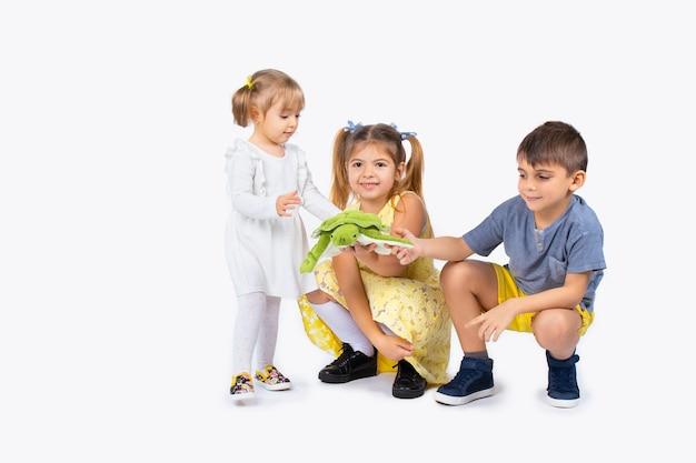 Не так пушистый питомец и дети на белом изолированном фоне с зеленой черепахой