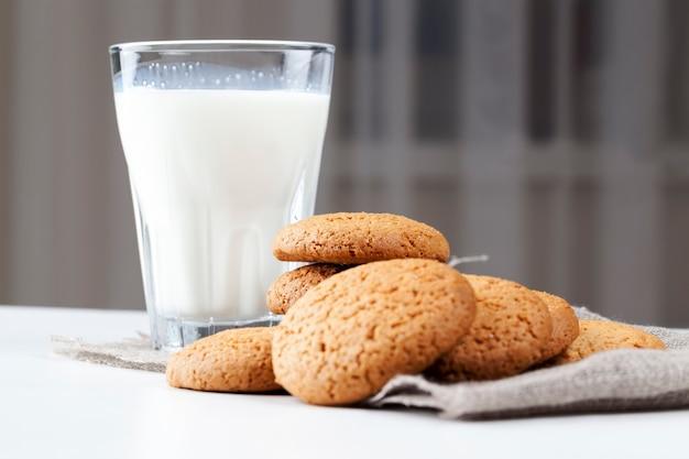 Не сладкое, а сухое и хрустящее печенье с добавлением сахара, твердое печенье, запеченное с овсяной и пшеничной мукой, низкокалорийное овсяное печенье на столе, стакан белого свежего молока