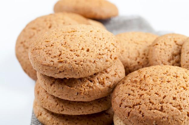 甘くてカリカリではないクッキー、本物の丸いクッキーの多孔質構造、小麦とオーツ麦粉から作られた丸いクッキー、クローズアップ