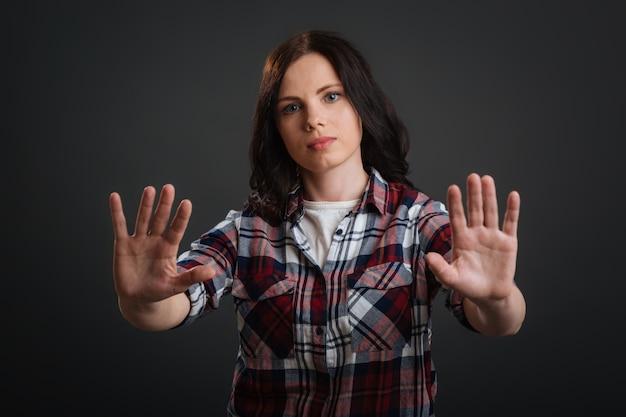 더 이상 받아들이지 마십시오. 일반적으로 알려진 제스처를 사용하여 금지 된 것을 인식하게 만드는 단호한 자신감있는 젊은 여성