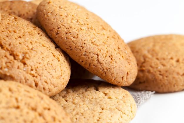 Не очень сладкое сухое и хрустящее печенье, пористое печенье, запеченное с овсянкой, крупный план - не очень калорийное овсяное печенье