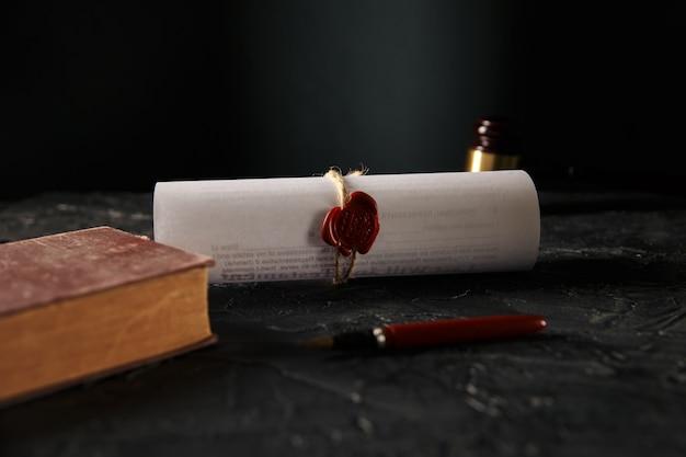 Нотариальная концепция. юридическая книга и договор с сургучной печатью и ручкой на столе.