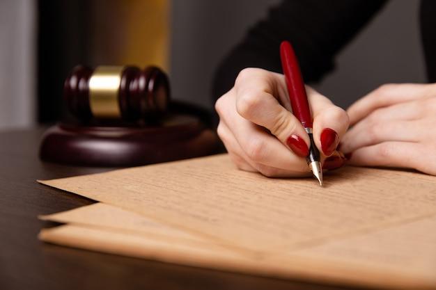 Нотариус в офисе подписывает документ
