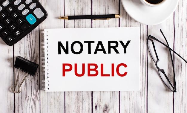 Notary publicは、電卓、コーヒー、メガネ、ペンの近くの白いメモ帳に書かれています。ビジネスコンセプト