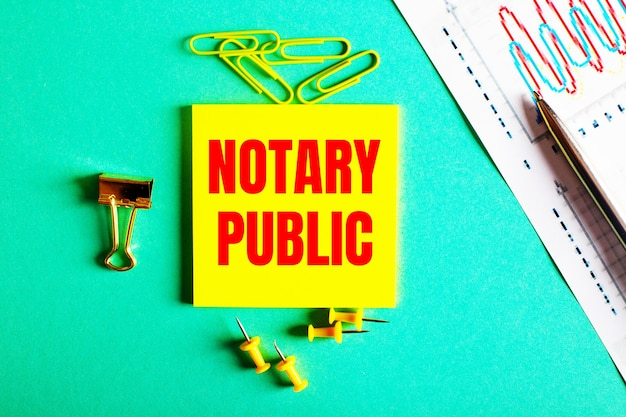 Notary public is written in red on a yellow sticker on a green surface near the graph and pencil