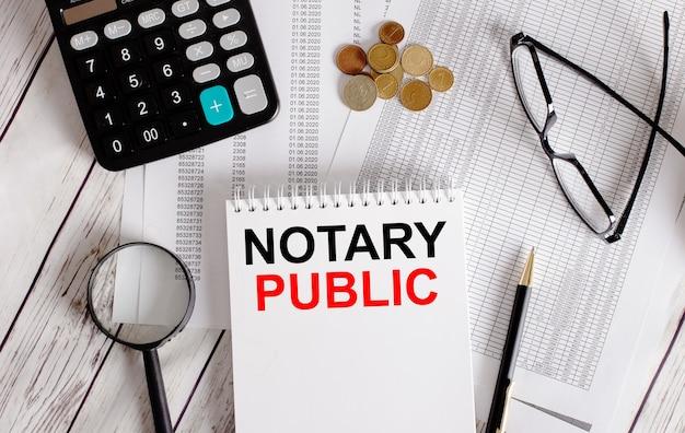 電卓、現金、眼鏡、虫眼鏡、ペンの近くの白いメモ帳に書かれた公証人。ビジネスコンセプト