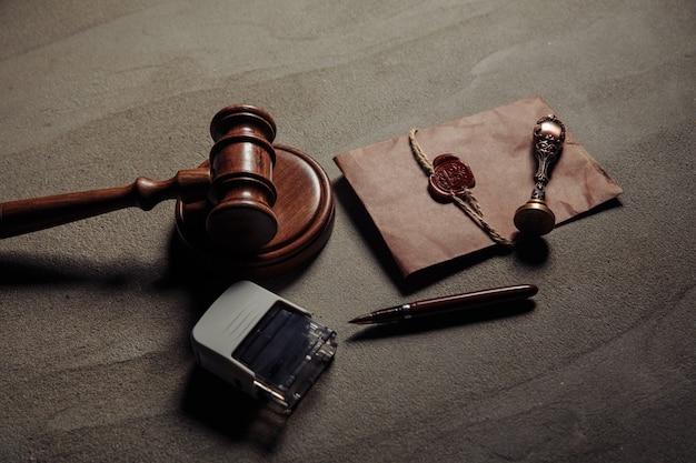 Нотариальная печать, деревянный молоток, нотариально заверенный документ на столе. понятие законности.