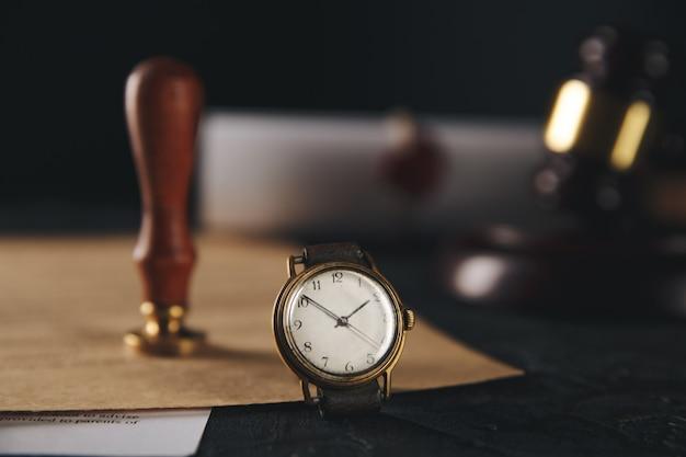 公証人のスタンプとテーブルの上の時計と木製の小槌