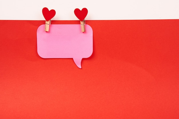 Примечание и деревянные прищепки красное сердце день святого валентина и красный лист бумаги изолировали фон.