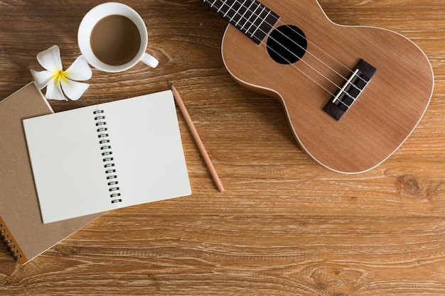 Note book ,cup of coffee and ukulele on table