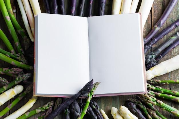 Записная книжка для рецепта здоровых блюд на фоне свежих спелых органических овощей спаржи.