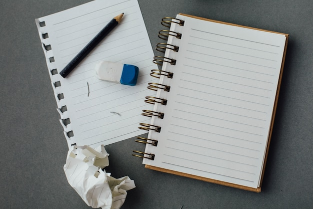 Note book and pencil on gray background