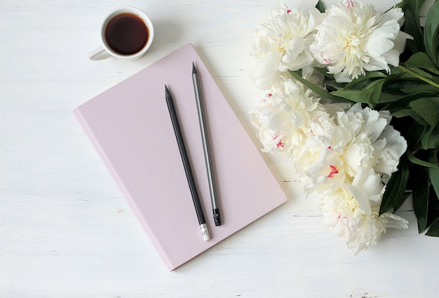 Note book, peonies and cup of coffee on light wood