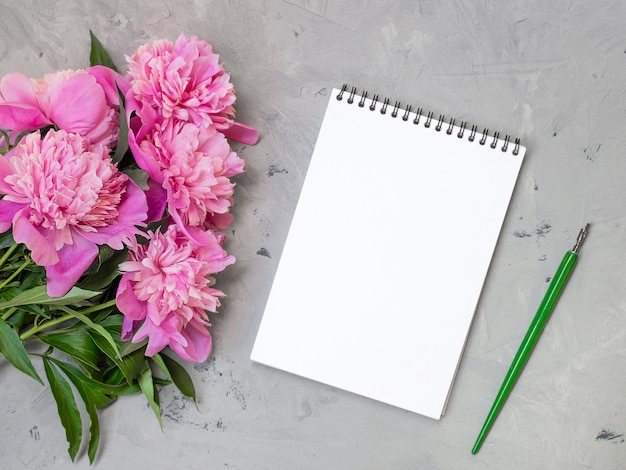 Note book with pink peonies on a stone background, copy space for your text top view and flat lay style.