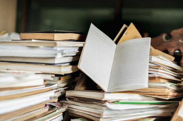 Note book with stack of old books on wooden table,