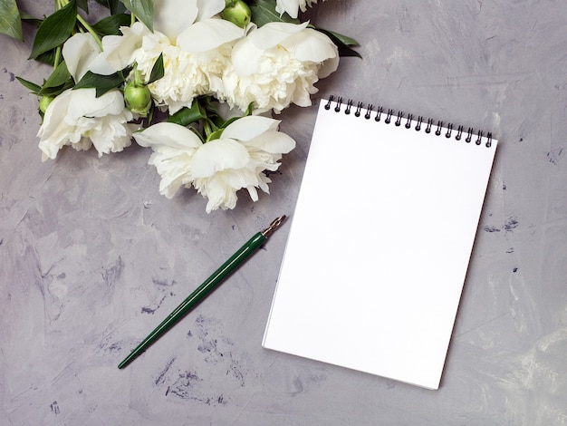 Note book with white peonies on a stone background, copy space for your text top view and flat lay style.