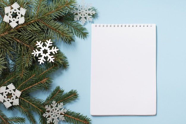 Note book with wish list. snowy fir branches on blue , copycopyspace. christmas and winter concept.