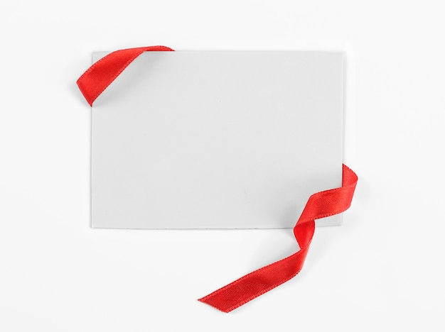 Note card with red ribbon on white surface