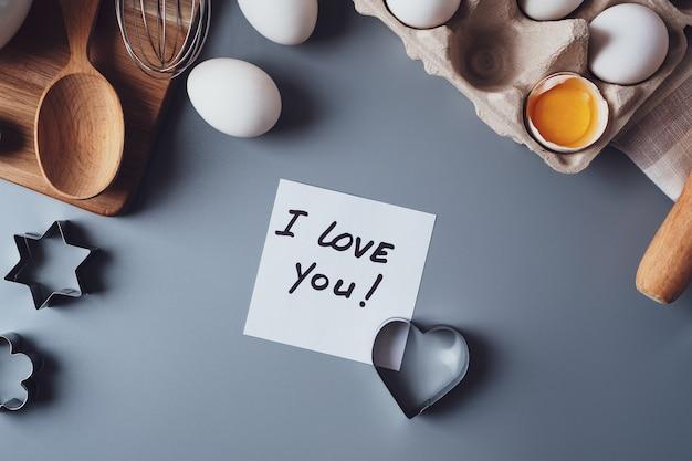 私はあなたを愛していることに注意してください。灰色の背景に自家製クッキーを作るための材料。バレンタインデー、父の日、母の日のお菓子を作るというコンセプト。フラットレイ、上面図。