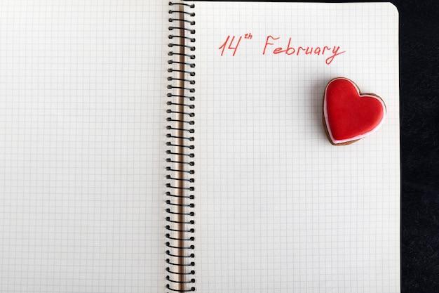 ノートブックに関する注記:2月14日とハート型のクッキー。バレンタインデー。