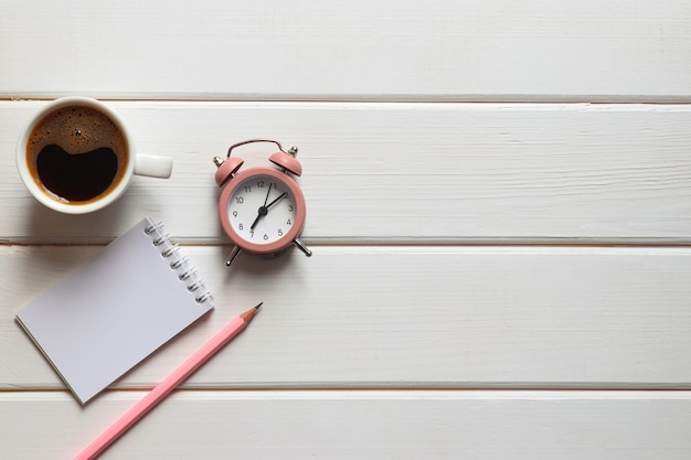 メモ帳、目覚まし時計、コーヒー、鉛筆、コピースペースのある木製のテーブル