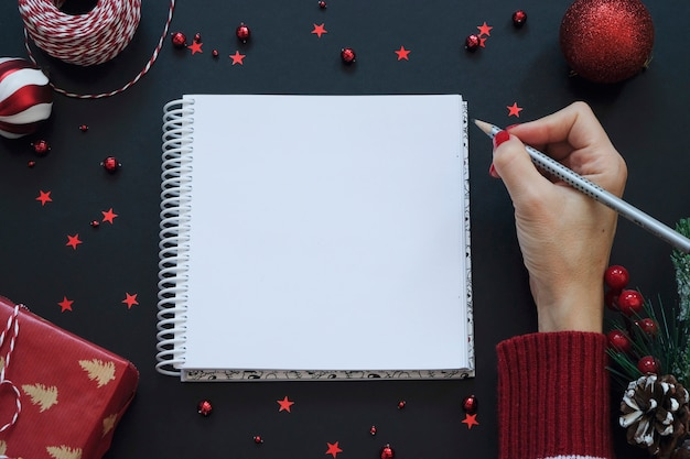 Note pad on black festive background with red decoration. christmas concept
