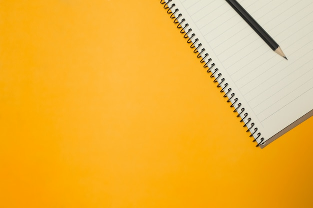 Note pad and pencil on the color background
