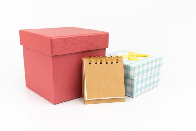 白い背景の上の2つのギフトボックスと紙またはカレンダーに注意してください。ギフトコンセプト。