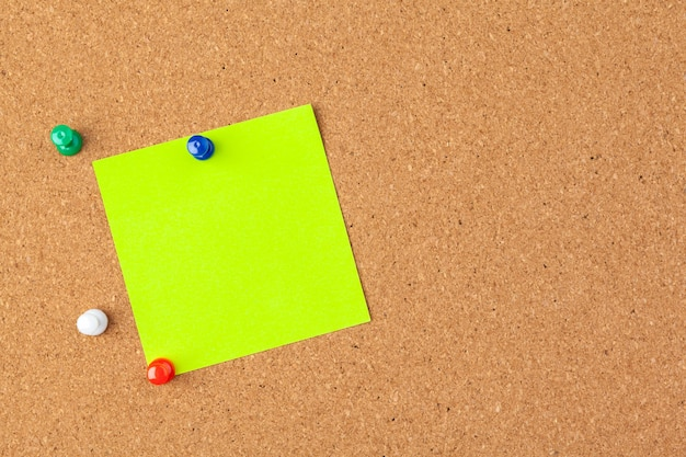 Note paper pined on brown cork board background