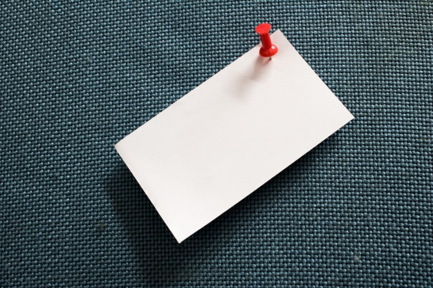 Note paper  and red pushpin into blue corkboard with copy space