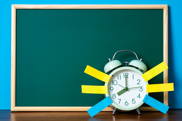 Note paper sticky and vintage alarm clock and blank green chalkboard on table with copy space
