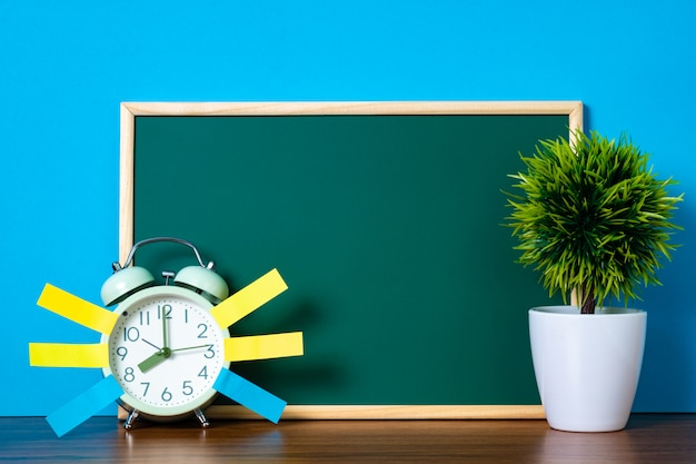 Note paper sticky and vintage alarm clock and blank green chalkboard