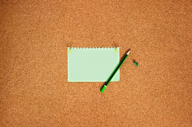 Note paper with green buttons and a cork board pencil, top view