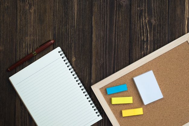 Note paper with pen and note pad on wood
