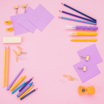 Note papers; color pencils and paper clips over pink backdrop