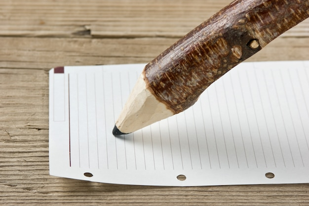 Note and pencil on wooden background